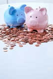 Piggy banks standing on coins. Two piggy banks standing among pile of coins Royalty Free Stock Photography