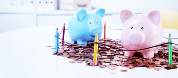 Piggy banks standing on pile of coins. Two piggy banks standing on pile of coins behind colored pencils fence Royalty Free Stock Image