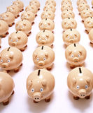 Piggy Banks Superannuation Finance. Many piggy banks lined up in rows on a white surface Stock Image