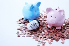 Piggy banks with thermostatic valve among coins. Two piggy banks with thermostatic radiator valve on saved coins Royalty Free Stock Photography