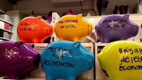 Piggy banks. Two rows of pottery piggy banks in assorted bright colours with captions written in French Stock Photography