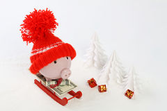 Piggy box with red hat with pompom standing on red sled with blanket from greenback hunderd dollars on snow and around are snowbou. Nd trees and three gifts with Royalty Free Stock Image