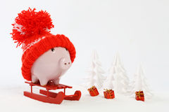 Piggy box with red hat with pompom standing on red sled on snow and around are snowbound trees and three gifts with gold bow Royalty Free Stock Photo