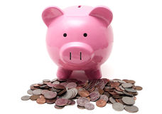 Piggy and Change. A pink piggy bank and a pile of change (in U.S. currency), isolated on a white background Stock Photo