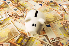 Piggy Coin Bank on fifity euro pile Stock Image