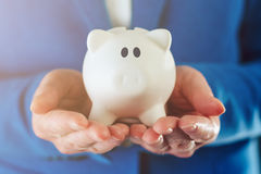 Piggy coin bank in hands of businesswoman Royalty Free Stock Image