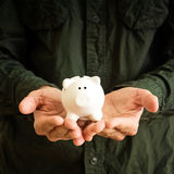 Piggy coin bank in hands Stock Image