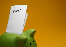 Piggy IOU. A green piggy bank on yellow background, shot slightly from the side note saying IOU Stock Photography