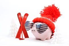 Piggy Kasten mit rotem Hut mit Pompom und Sonnenbrille formt Herz mit USA-Flagge, die nahe bei rotem Ski und Skistöcken auf Schne Stockfotografie