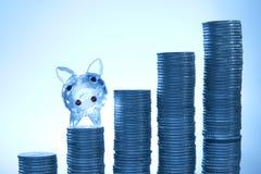 Piggy mit Münzen auf blauem Hintergrund Stockfotografie