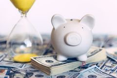 Piggy moneybox with dollar cash. And sand clock closeup. Financial concept Stock Photos