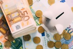 Piggy moneybox with euro cash. And coins closeup. Financial concept Stock Photos