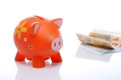 Piggy orange with banknote Stock Photos
