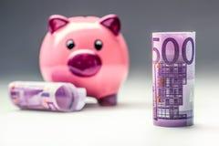 Piggy packa ihop Rosa Piggy räddning och femhundra eurosedlar tonat foto Fotografering för Bildbyråer