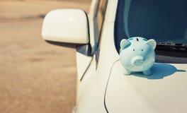 Piggy pengarbank p? huven av en ny vit bil royaltyfri fotografi