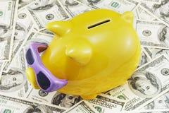 Piggy Querneigung auf Dollar lizenzfreie stockfotos