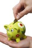 Piggy Querneigung auf einer Hand Lizenzfreie Stockfotografie