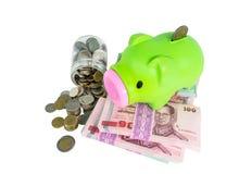 Piggy Querneigung auf Geld lizenzfreie stockfotografie