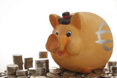 Piggy Querneigung auf Münzen Lizenzfreie Stockfotos
