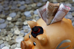 Piggy Querneigung auf Münzen Stockfotografie