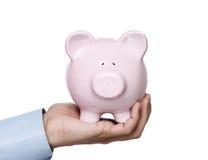 Piggy Querneigung in der Hand Lizenzfreie Stockbilder
