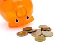 Piggy Querneigung gedreht mit Münzen Stockbild