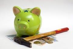 Piggy Querneigung, Geld und Hammer lizenzfreie stockbilder