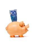 Piggy Querneigung mit Anmerkung des Euro 10 Lizenzfreie Stockfotografie