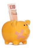 Piggy Querneigung mit Anmerkung des Pflasters und 10 Pfund Lizenzfreies Stockfoto