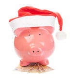 Piggy Querneigung mit dem Weihnachtshut, der auf Euros steht stockbild