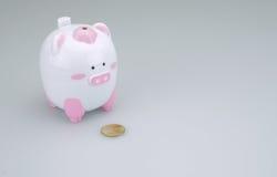 Piggy Querneigung mit einer Münze stockfotos