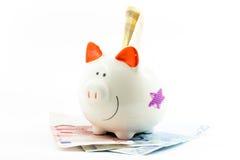 Piggy Querneigung mit Eurobargeld Stockfoto