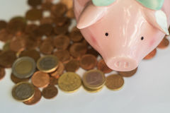 Piggy Querneigung mit Euromünzen Stockbilder