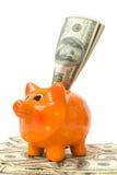 Piggy Querneigung mit Geld Lizenzfreie Stockfotos