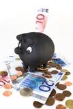 Piggy Querneigung mit Rechnungen und Münzen lizenzfreies stockbild