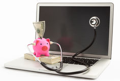 Piggy Querneigung mit Stethoskop auf Laptop Lizenzfreie Stockfotografie
