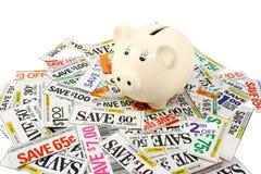 Piggy Querneigung mit vielen Lebensmittelgeschäft-Kupons Lizenzfreies Stockfoto