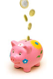 Piggy Querneigung-Münzen Stockfoto