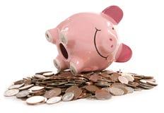Piggy Querneigung moneybox mit britischen Bargeldmünzen Lizenzfreie Stockfotografie