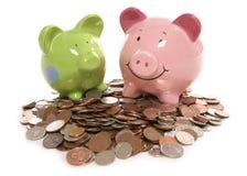 Piggy Querneigung moneybox mit britischen Bargeldmünzen Stockbilder