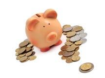 Piggy Querneigung umgeben durch Münzen in einem Fragezeichen stockfotos