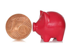 Piggy Querneigung und eine eurocent Lizenzfreies Stockfoto
