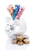 Piggy Querneigung und Eurogeld lizenzfreie stockfotografie