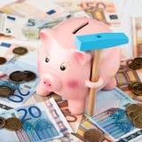 Piggy Querneigung und Eurogeld lizenzfreie stockbilder