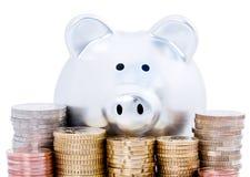 Piggy Querneigung und Euromünzen Stockfoto