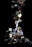 Piggy Querneigung und fallende Münzen Stockbilder