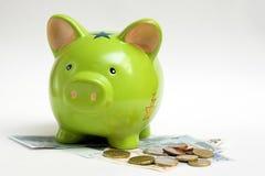 Piggy Querneigung und Geld Stockbild