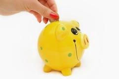 Piggy Querneigung und Hand mit der Münze getrennt auf weißem Ba Lizenzfreies Stockfoto