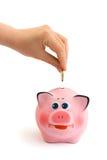 Piggy Querneigung und Hand mit Münze Stockfotografie