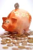 Piggy Querneigung und Lots Münzen stockfotos
